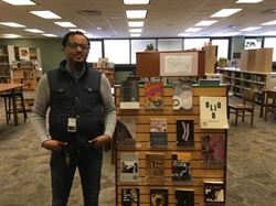 Chaun Webster is pictures standing next to a poetry display