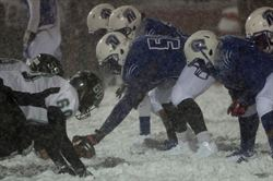 Two football teams crouched at the line and playing in snow