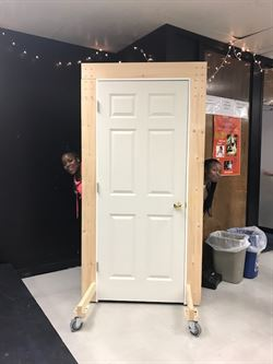 White door with two students peeking out from the side.