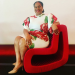 Ms. Bell sitting on a red chair with a red and white flowered dress